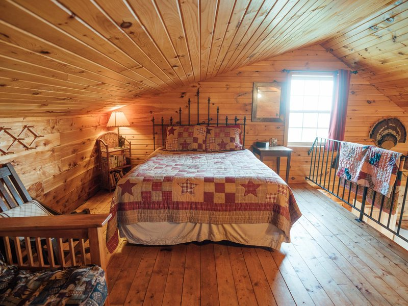 One of the two queen beds in the cabin's loft area.