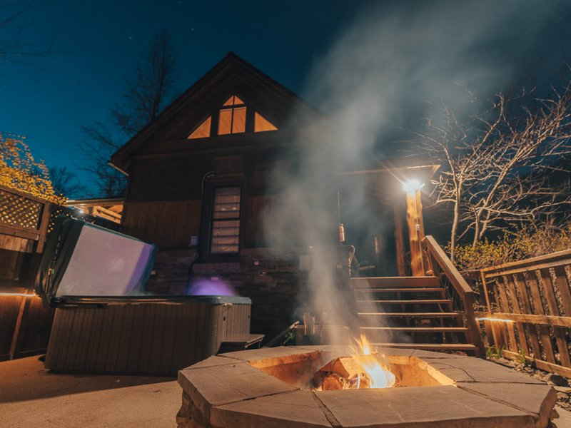 The patio of the Creekside Cabin with fire pit, hot tub, and Grill.
