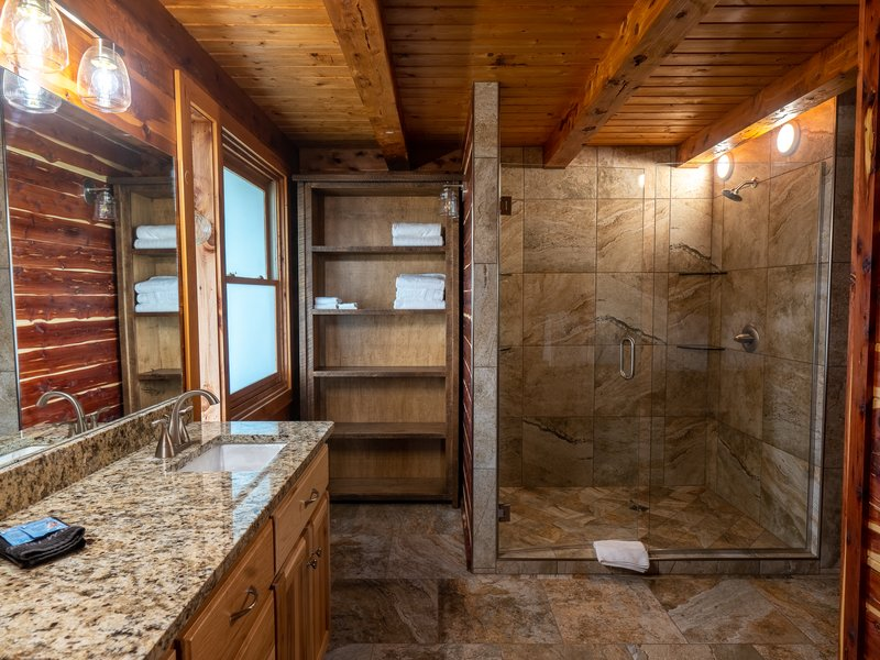 The cabin's main floor bath featuring stone-tiled shower