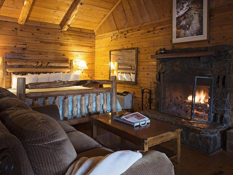 The Valley Secret Cabin features a king-size bed near a nativestone fireplace