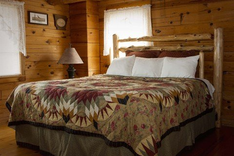 The main bedroom of the Arkansas Cabin features a king-size bed with large, adjoining shower bath.