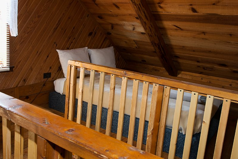 The cabin's loft features two full-size beds, one on each side of the stairway.