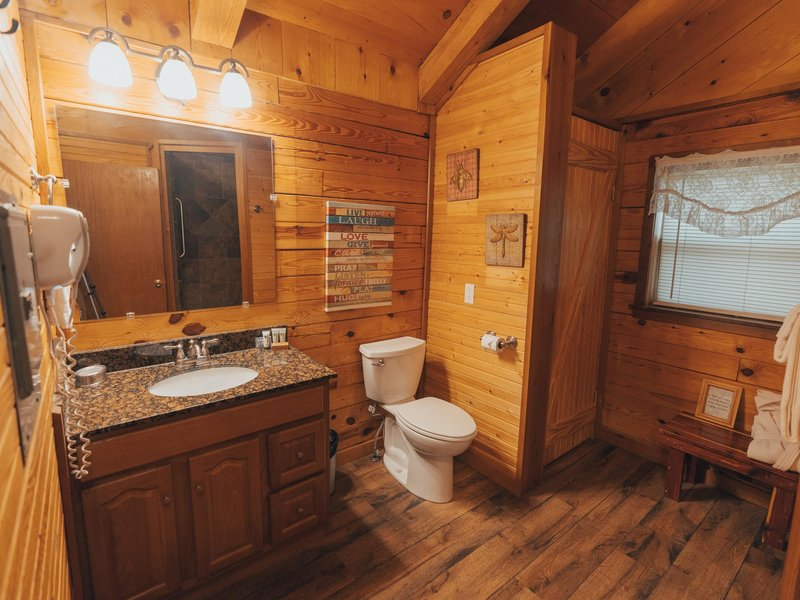 The Mountain Sunrise cabin features a bath with hair dryer, linens and stone tile shower.