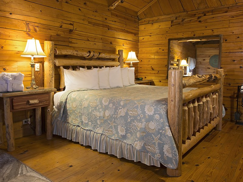 The cabin's king-size bed offers nearby fireplace and soaking tub ambience.