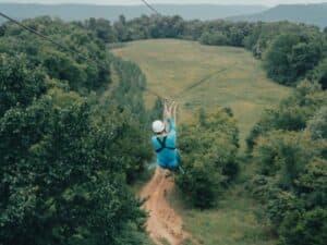 Man zip lining through trees
