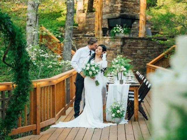 A wedding couple on the back deck. The beautiful exterior of the Ponca Creek Lodge makes it a great location for outdoor weddings and receptions