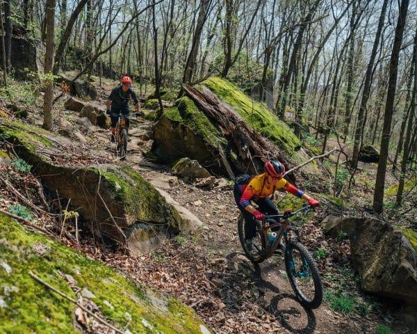 Mountain bike riders making their way through boulders along the BOC Ponca Downhill MTB Trail.