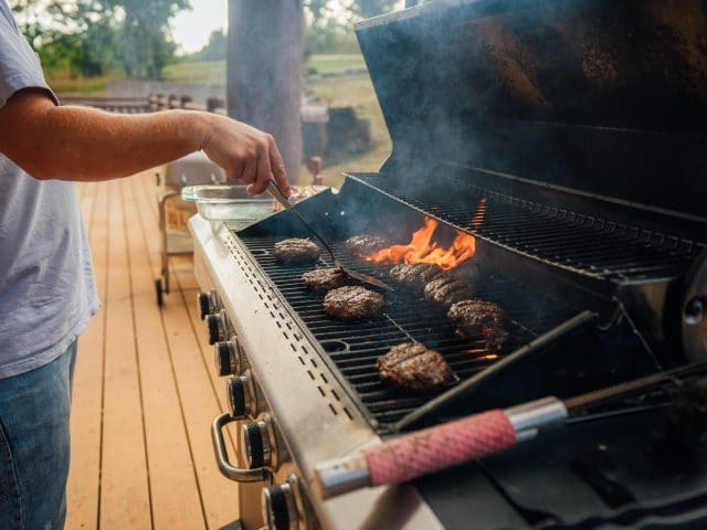 A guest flipping burgers on the large grill at Riverwind Lodge