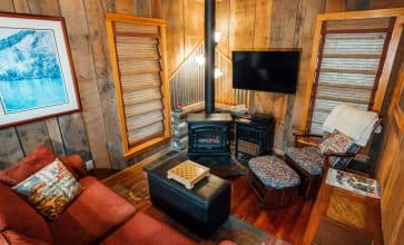 The Creekside Cabin features a cozy living area with with an electric fireplace.