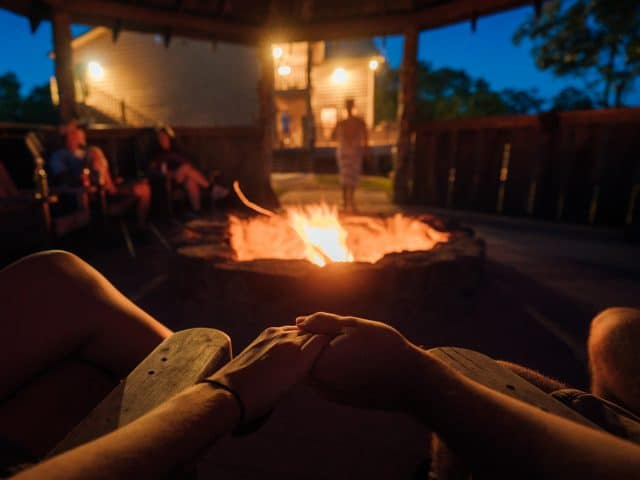 A family gathered around the fire-pit at the Riverwind Lodge