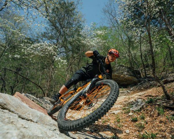 A mountain bike rider coming through a berm on the BOC Ponca Downhill MTB Trail.