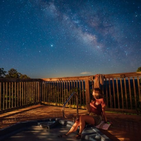 A girl views the Milky Way from the Riverwind Lodge hot-tub.