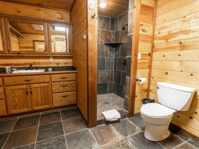 The beautiful master bathroom of the Mountain Sunset Cabin with slate and river rock walk-in shower.
