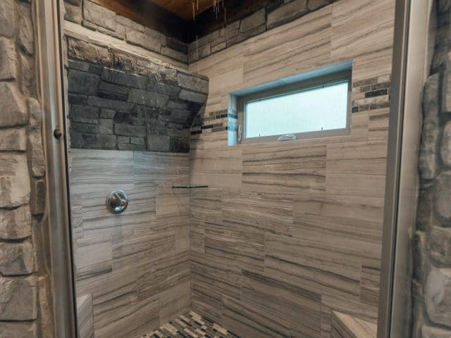 This cabin's beautiful, rustic bathroom features a gorgeous walk-in waterfall shower.