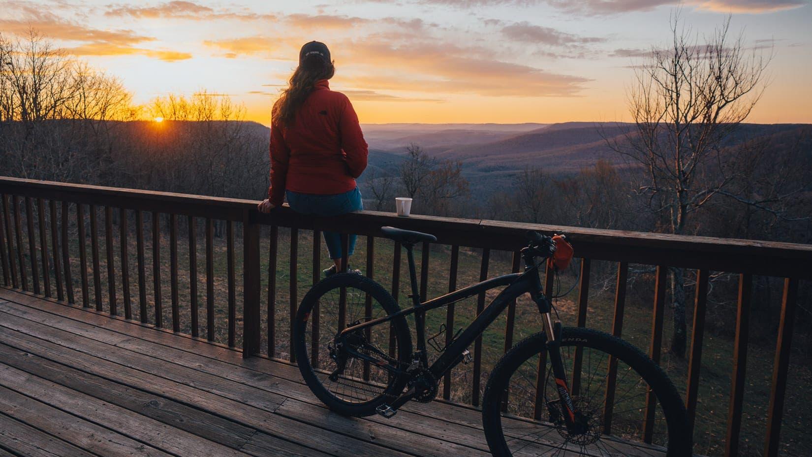 woman by bike watching a sunset