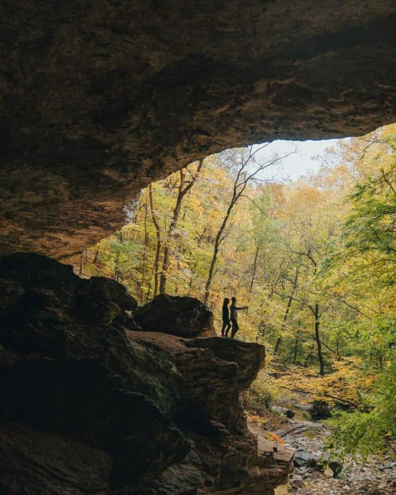 Two hikers surrounded by a cave opening.