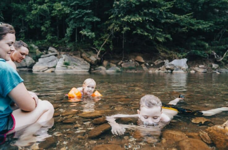 two kids playing at a swimming hole