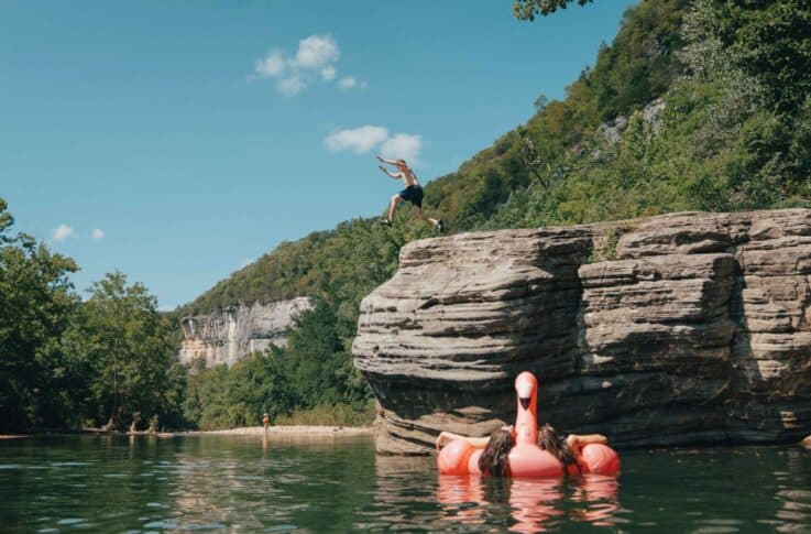 jumping off a rock into a swimming hole