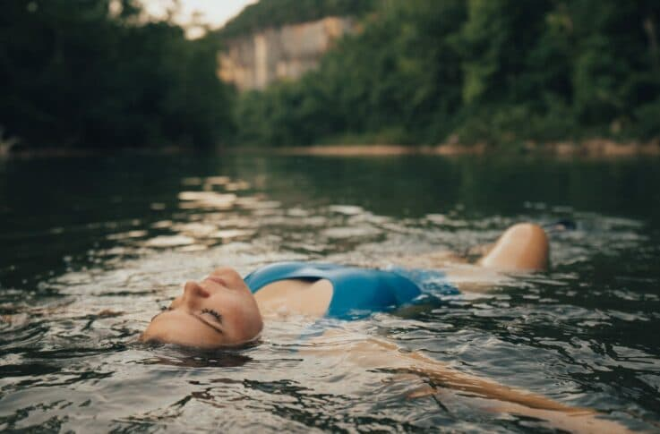 Young woman floating at a swimming hole