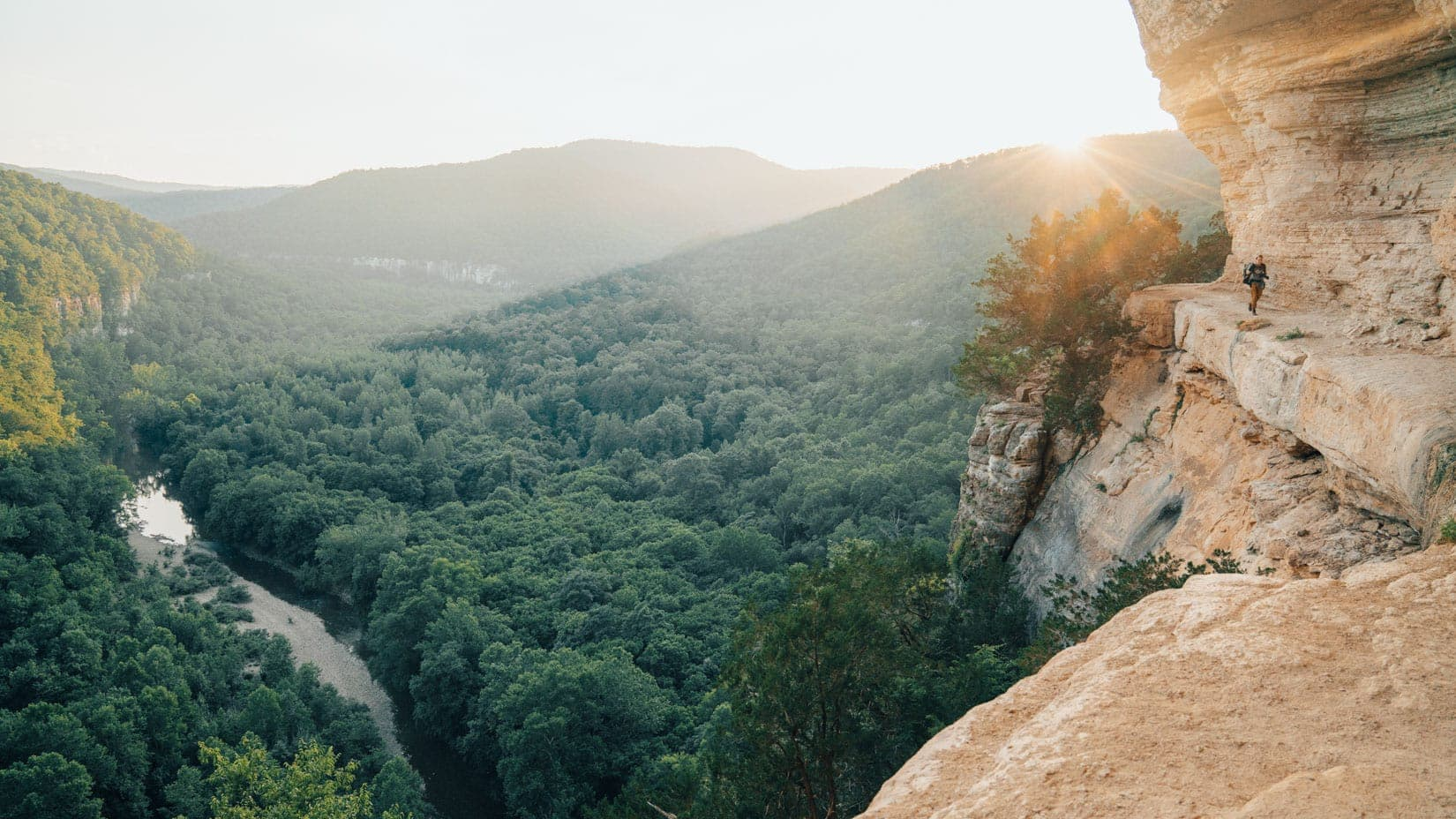 Hiker on a cliff at sunset
