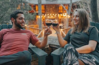 A couple drinking wine by a cabin