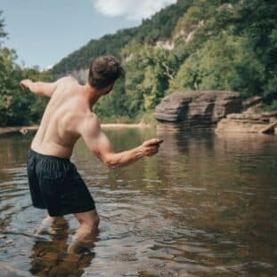 Young adult skipping rocks in a river