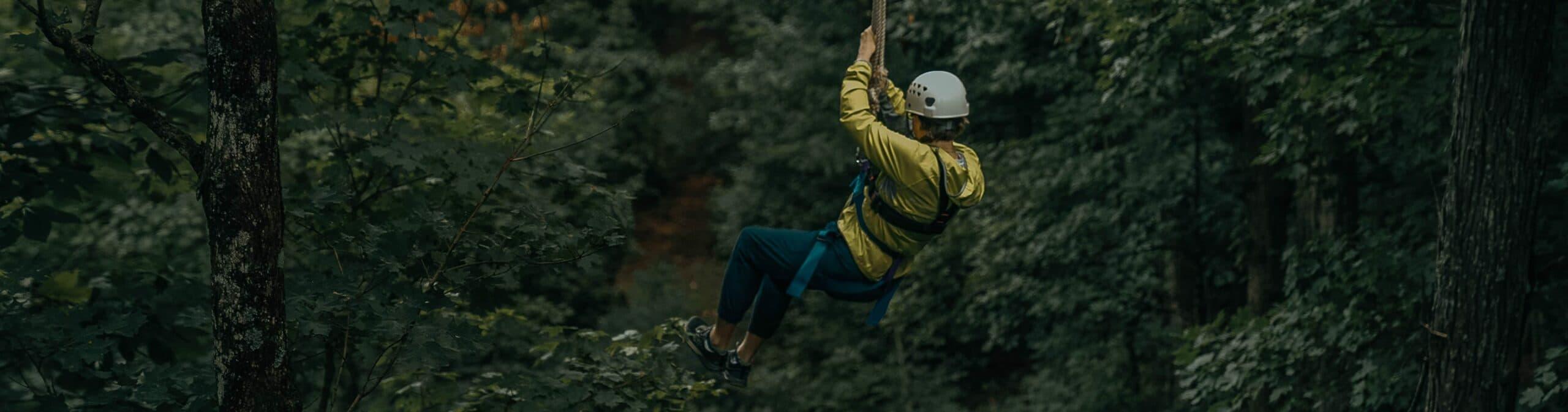 Woman zip lining through trees
