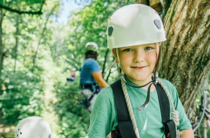 A kid smiles while on the platform of the Buffalo River Canopy Tour.