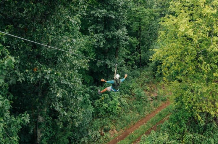Man with arms out on the Buffalo River Canopy Tour.