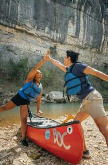 Two friends giving a high-five during their float along the Buffalo National River.
