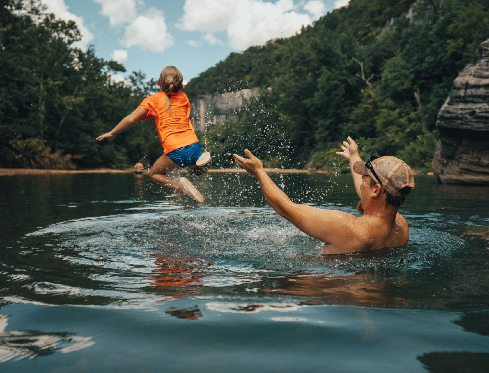 Father launching child into water at a swimming hole