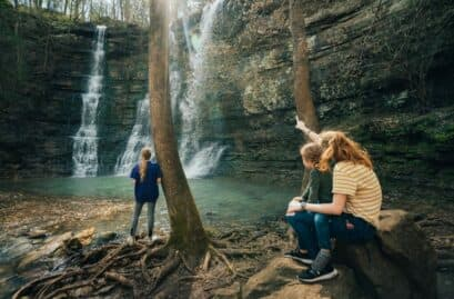 a mother and children admiring a waterfall
