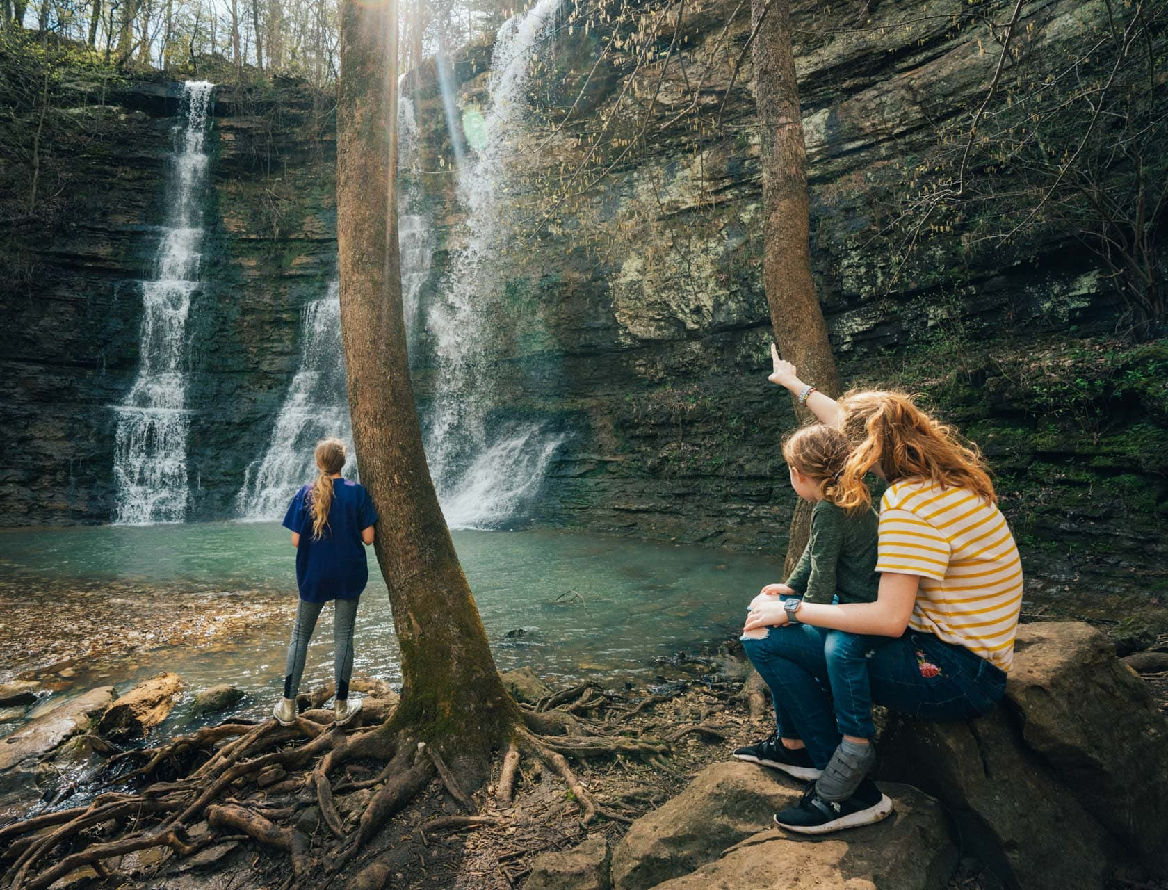 A mom and her children admiring a Buffalo River country waterfall.