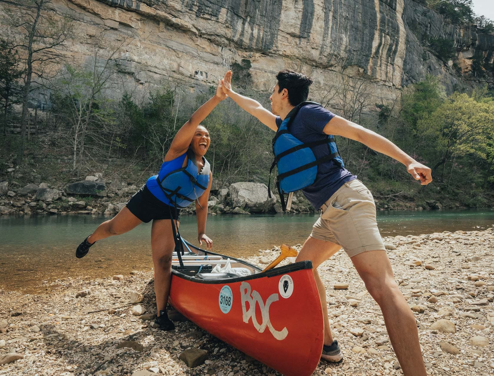 two friends high fiving over a canoe