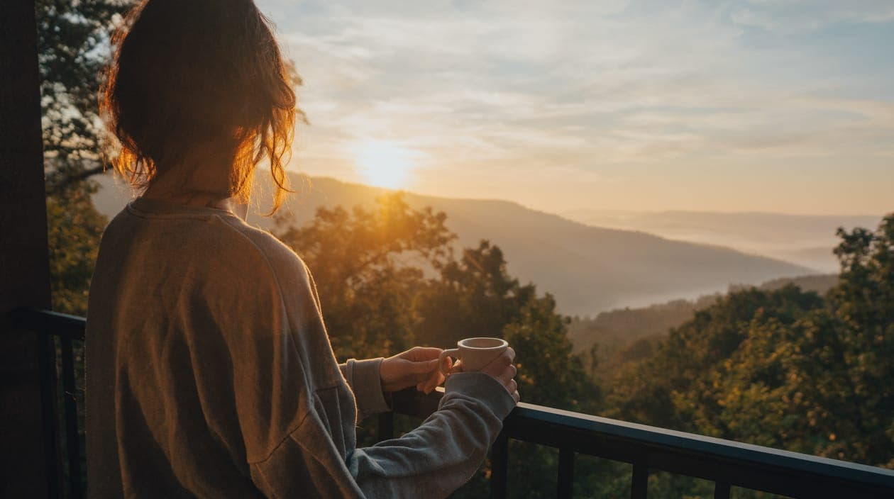 woman with coffee admiring a sunset