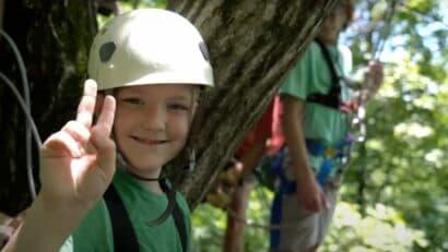 zipline boy giving the peace sign
