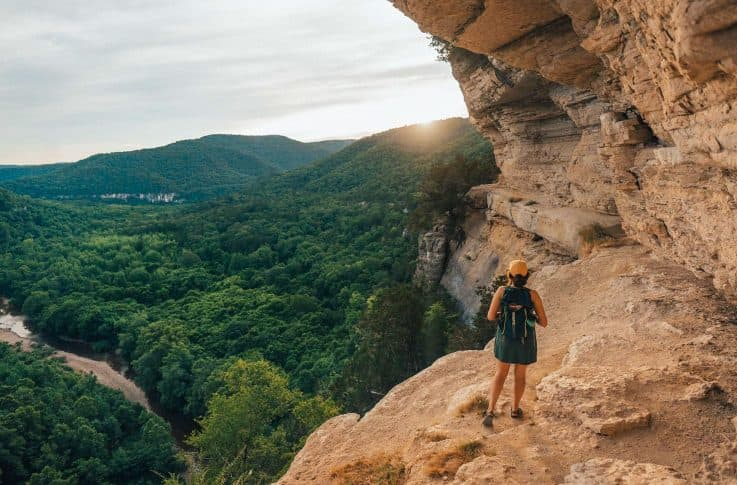 woman hiking along a steep ledge overlooking mountains