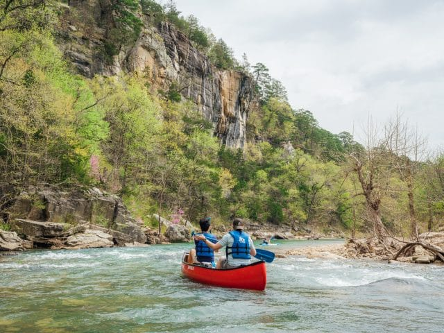 Floaters paddling below a bluff on the Buffalo National River in Arkansas..
