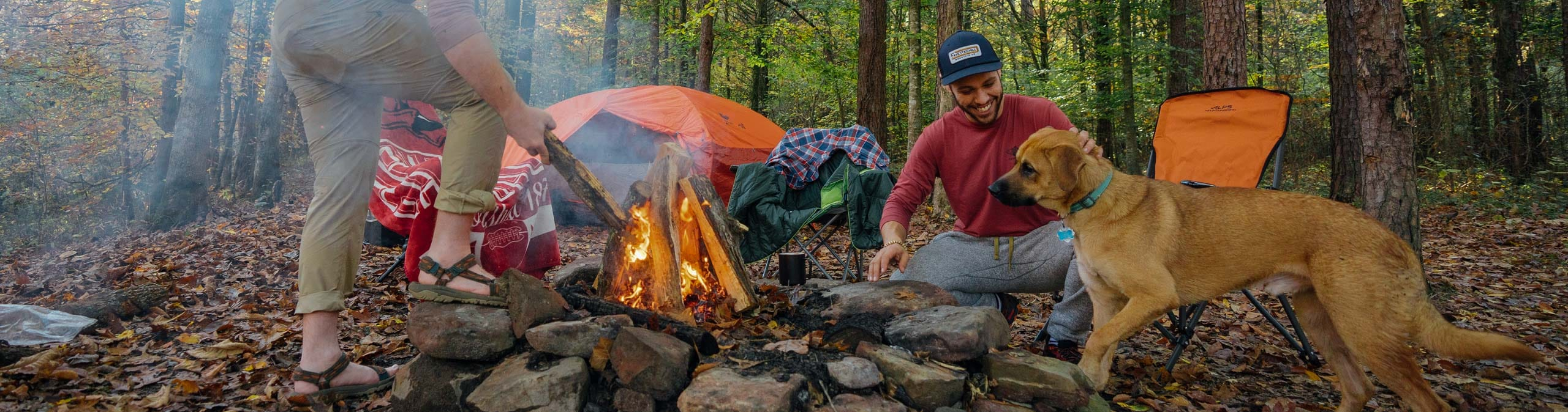 two men and a dog building a fire while camping