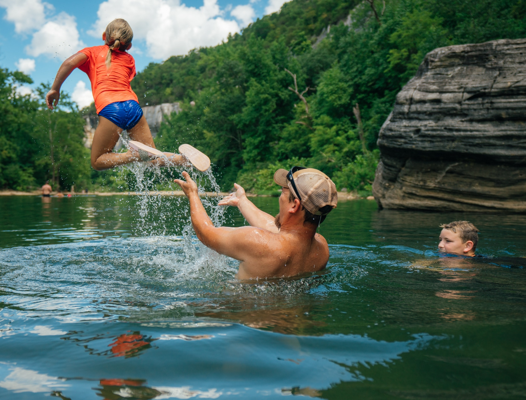 A family playing in a beautiful Buffalo River swimming hole during summer.