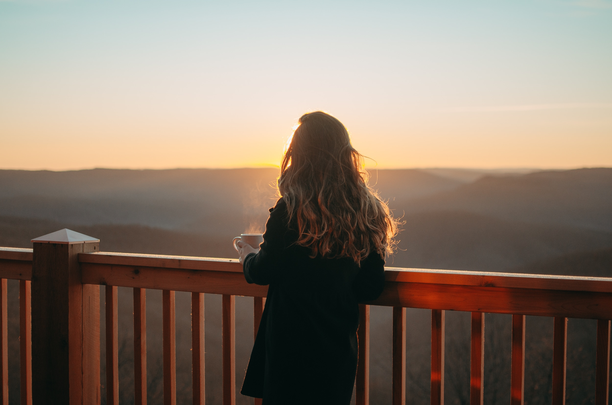 A woman with long brown hair enjoying a hot beverage and the view of the Buffalo River country from the cabin deck